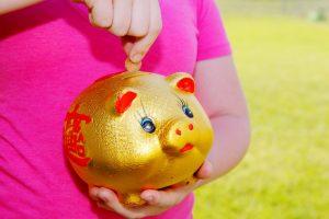Girl_Purring_Money_Into_Piggy_Bank