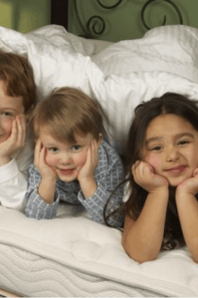 kids on a bed with hands on face elbows