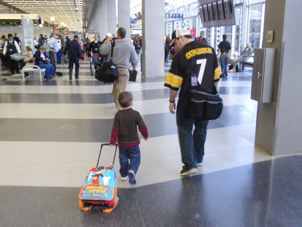 the importance of family travel - father and son in airport - Pittsburgh Steelers Fan
