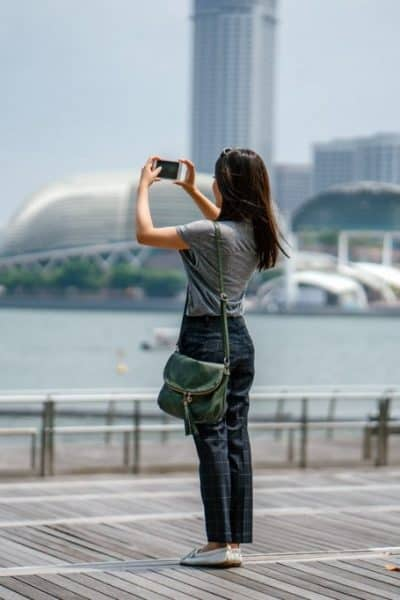 woman taking picture on vacation river city tourist