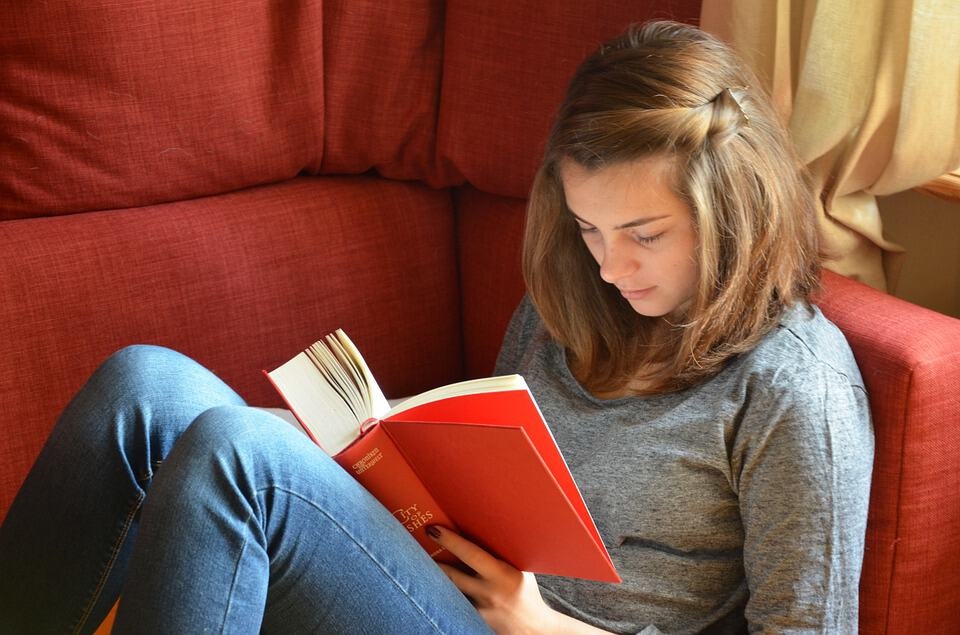 girl curled up reading a book - health and wellness self care tips