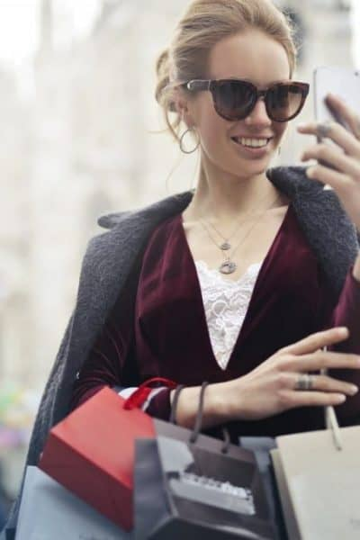 women shopping with bags holding phone for post on how to find local deals