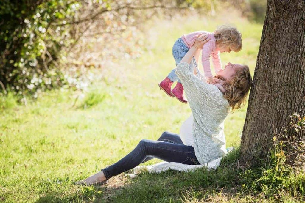 mother and child in park under tree