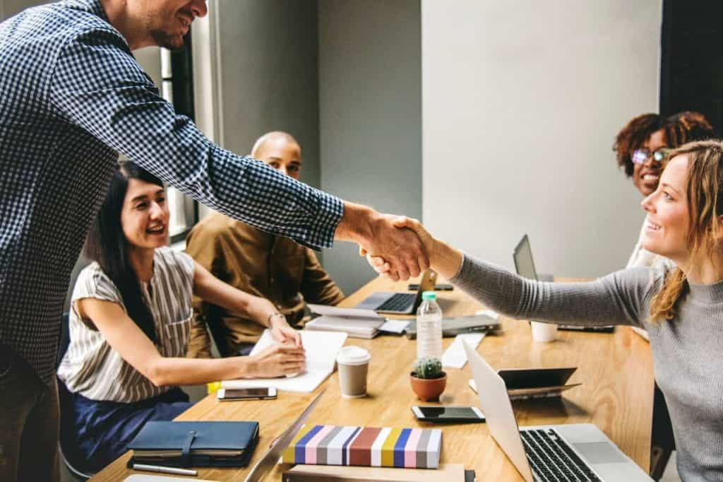colleagues meet in conference room at office shake hands