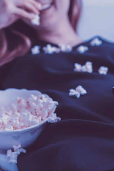 woman eating popcorn on couch sofa
