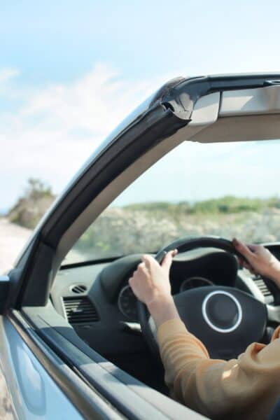 woman driving convertible car in desert